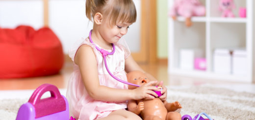child girl playing doctor with toy at home