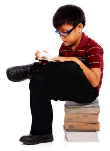 Intelligent Boy Sitting On A Pile Of Books And Reading One