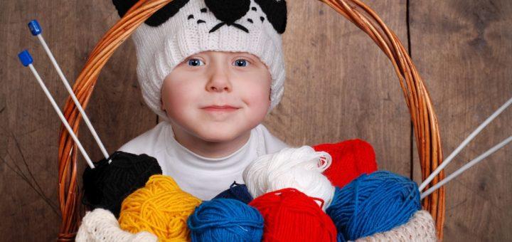 12029462 - little boy in knitting panda hat with wool yarn into basket